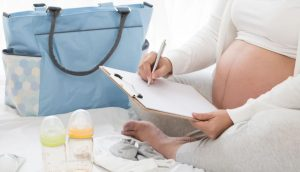 pregnant woman writing list with blue bag