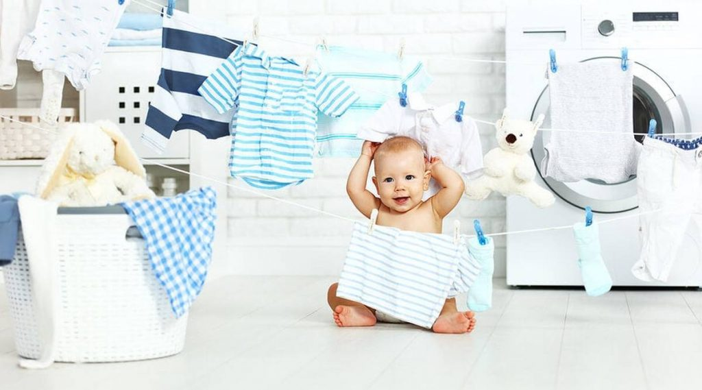 baby amongst washed clothes and clothing line