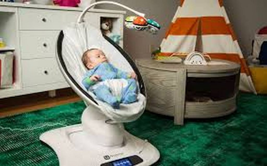 baby in baby bouncer with mobile attachment