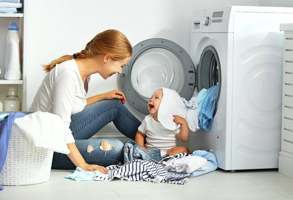 happy mother and baby sitting in front of washing machine