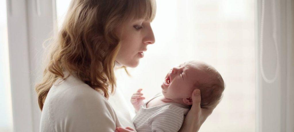 mum holding crying baby