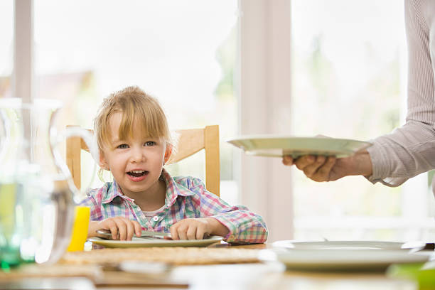 young mother is setting the table for her family for lunch.