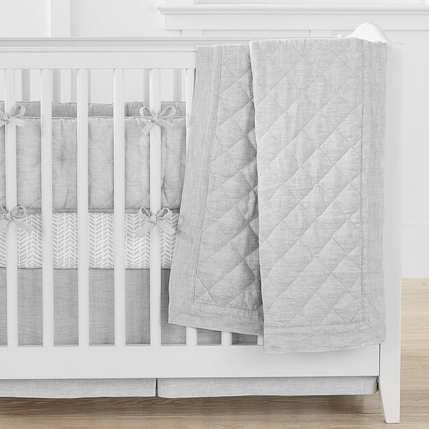 white cot with light grey bedding